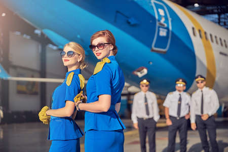 Stylish females stewardesses in sunglasses felling happy while working in the airport