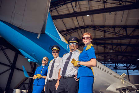 Two females air hostess and two handsome men posing at the photo camera in front of passenger airplane