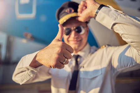 Pilot in white shirt holding the hat while another hand gesturing int he outdoors