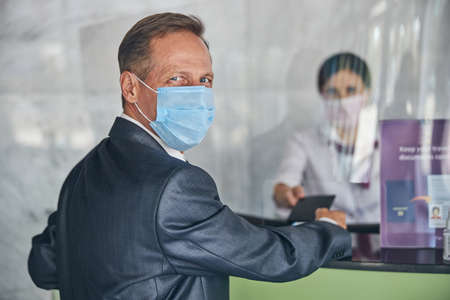 Cheerful businessman checking in at airport during pandemic