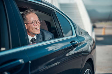 Smiling businessman leaving airport in car with driver