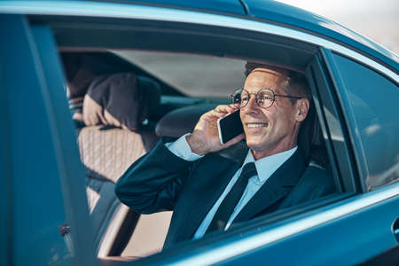 Cheerful businessman talking on smartphone during transfer from airport Imagens