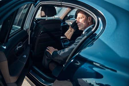 Handsome mature businessman sitting in comfortable car 版權商用圖片
