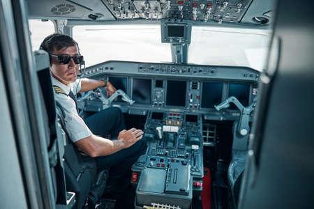 Smiling handsome pilot sitting in plane cockpit Banque d'images