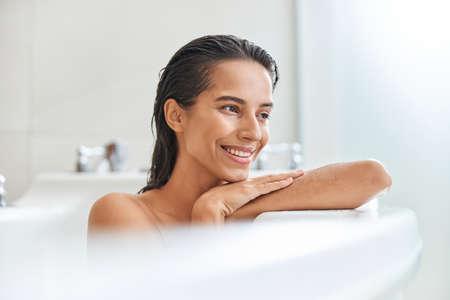 Joyful young woman taking bath at home