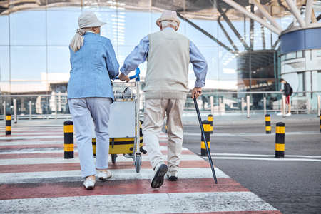 Senior couple with baggage approaching the airport terminal Banque d'images