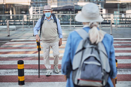 Senior tourists crossing the road in opposite directions