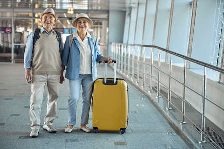 Joyous tourist couple standing at the airport