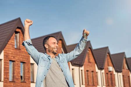 Joyful brunette man celebrating getting a new house