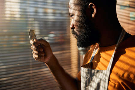 Bearded Afro American man holding portable hair trimmer