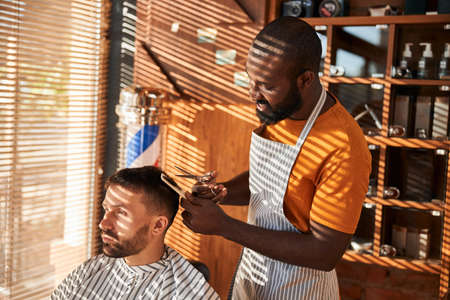 Cheerful barber cutting client hair with scissors in barbershop
