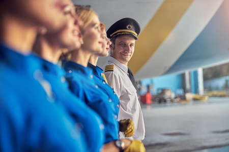 Flight team wearing respective blue and white uniforms standing near the airplane