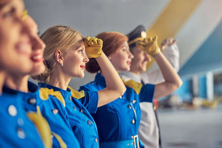 Blonde Caucasian woman air hostess in leather gloves in front of passenger airplane