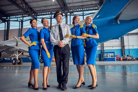 Smiling cheerful four stewardesses with handsome pilot in stylish uniform Stock fotó