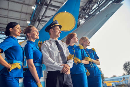 Handsome pilot and four air hostesses in stylish uniform looking into the distance