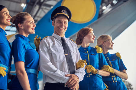 Adult confident male with four air hostess near the passenger aircraft