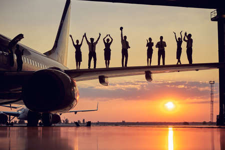 Happy friendly solid team of pilots and stewardesses isolated on sunset background Stock fotó