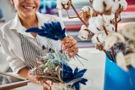 Pleasant female florist posing with some dry blue flowers 免版税图像