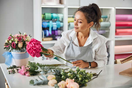 Enthusiastic female florist making a bouquet of pretty flowers