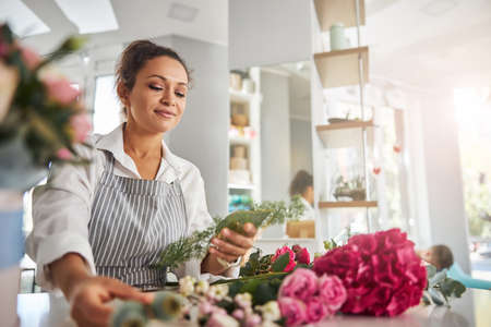 Concentrated female florist choosing flowers for floral creations 免版税图像