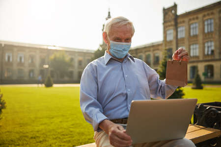Senior man checking health results online with laptop