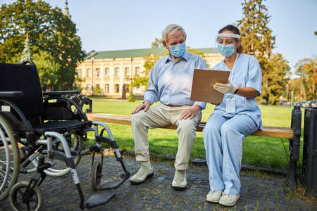 Doctor and old man looking at illness history