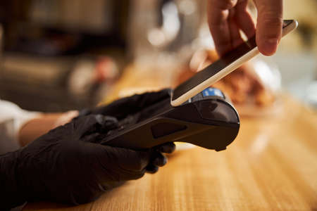 Barista holding payment machine while client paying by smartphone in coffee shop