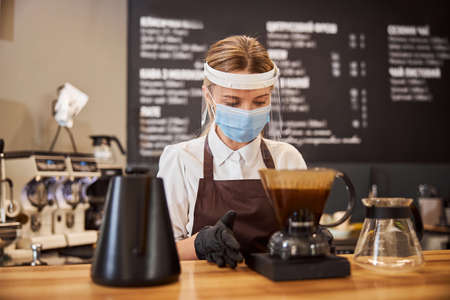 Cheerful female barista preparing coffee using chemex pour over coffee maker