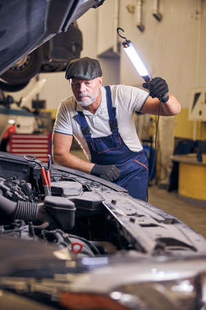 Bearded male worker inspecting car engine at service station
