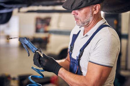 Serious auto mechanic using air blow gun at service garage Banco de Imagens