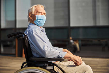 Old handicapped man in wheelchair with hands on armrests