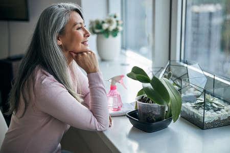 Charming woman sitting at windowsill with houseplants