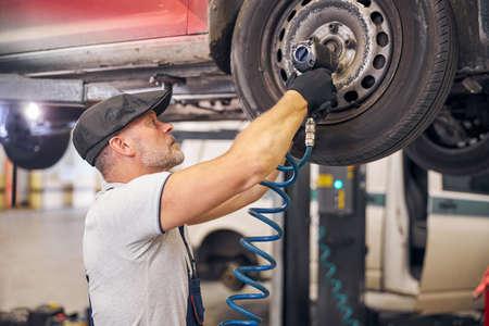 Bearded auto mechanic repairing car wheel disk in garage Banco de Imagens