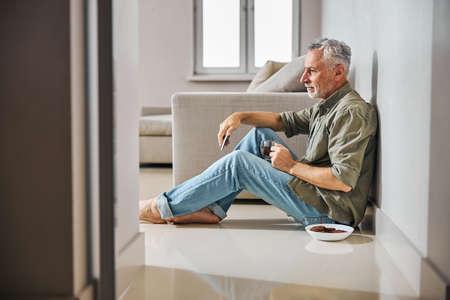 Grey-haired gentleman having tea with cookies on the floor