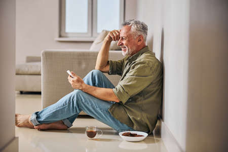 Joyous aged man smiling widely while having tea on floor