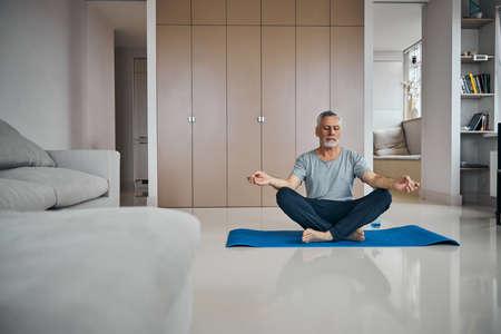 Mindful senior gentleman practising meditation at his house