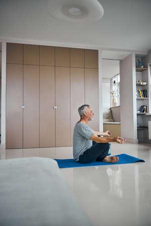 Elderly man practising meditation in his living room