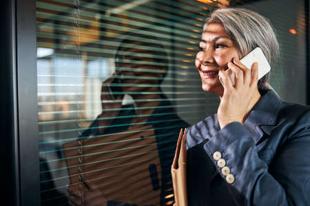 Cheerful woman talking on cellphone at work