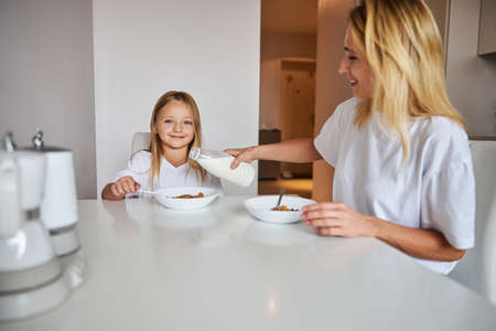 Little girl with mother eating at the dinner table in the morning Stockfoto