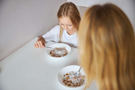 Mother with cute daughter sitting at the dinner table while eating tasty meal Stockfoto