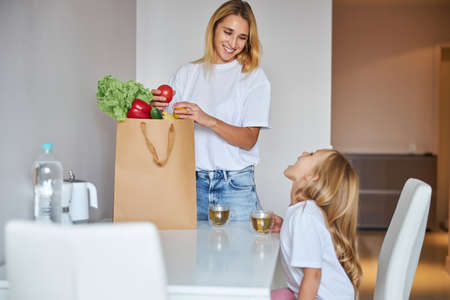 Happy cheerful mother with vegetables in paper shopping bags at home Stockfoto