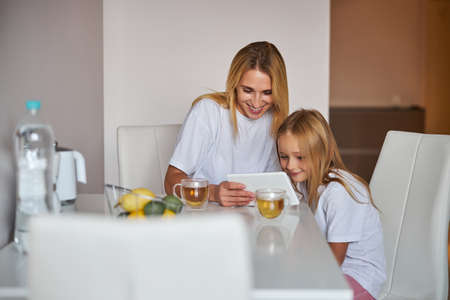 Happy smiling mother with daughter sitting at the white table and having fun together