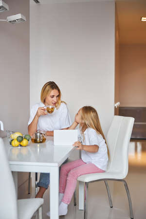 Happy cheerful mother talking with little daughter at the cup of tea in home kitchen Stockfoto
