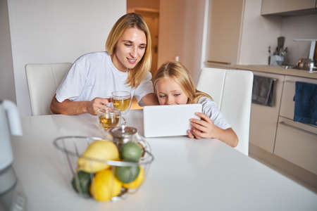 Young mother and small daughter using digital tablet in home kitchen Stockfoto