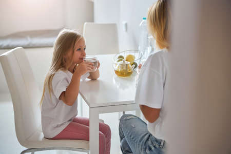 Lovely little girl looking to elegant clever woman and listening her in room inside Stockfoto