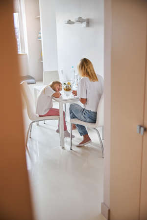 Little daughter putting head on the desk while listening her mother in living room