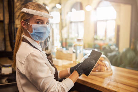 Cafe worker using modern device while making the bill