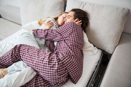 Happy loving couple sleeping and cuddling in bed Фото со стока