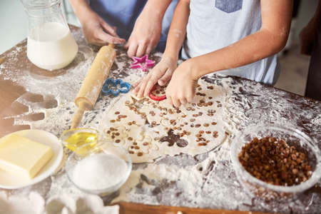 Kids covered in flour making cookie shapes out of dough