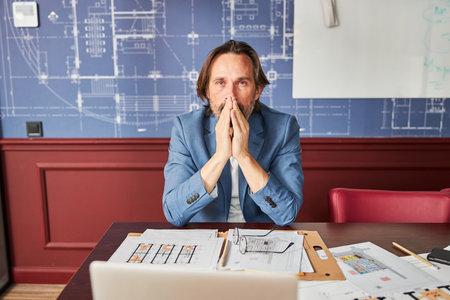 Overworked gentleman looking thoughtful in his office